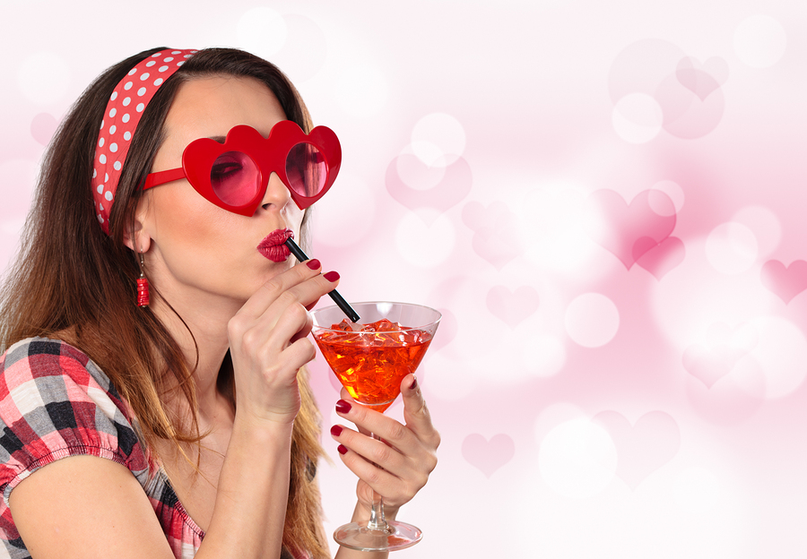 Young woman wearing heart shaped red glasses and drinking red cocktail.