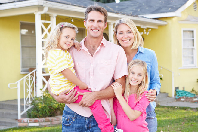 Family Standing Outside Suburban Home