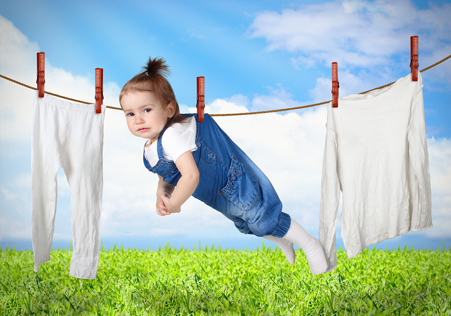 Funny child hanging on line with clothes laundry creative concept